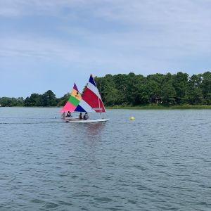 2 boats race toward yellow ball buoy