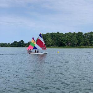 2 boats race toward yellow ball buoy