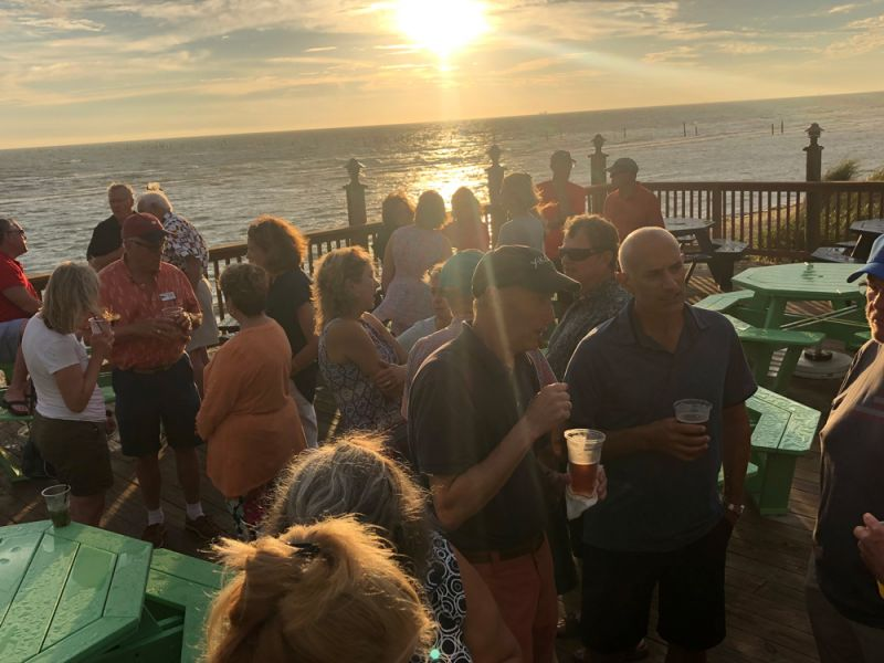 view of the fundraising crowd on the deck at sunset